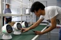 """An engineer of Lanchuang Network Technology Corp tests a """"Xiaoyi"""" robot, a Siri-like smart assistant, which links users to the intelligent elderly care system at the company's headquarters in Weifang, at the eastern coastal province of Shandong, on July 25. Photo: Reuters"""