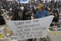 Protesters hold up a banner during a sit-in at Hong Kong airport on August 9. Photo: AP