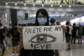 An anti-government protester makes her feelings known in the arrivals hall at Hong Kong International Airport on Monday. Photo: Sam Tsang