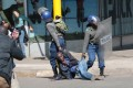 Zimbabwe Republic Police (ZRP) drag an injured protester during clashes in Harare on Friday. Photo: EPA-EFE
