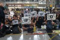 """Protesters at Hong Kong International Airport on August 12 chant """"police shot the girl, an eye for an eye"""" and hold up signs saying """"give back the eye"""", after a young woman was seriously injured during police firing of beanbag rounds in Tsim Sha Tsui the previous evening. Photo: Joanne Ma"""