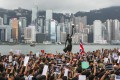 Protesters march past a view of the iconic Hong Kong skyline in Tsim Sha Tsui towards the West Kowloon high-speed rail terminus on July 7. Photo: Felix Wong