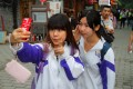 Students taking photos at Beijing's Nanluo Guxiang historic street.
