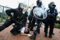 Police in riot gear restrain a protester outside the Legislative Council building in June. Photo: Felix Wong