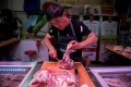 A butcher cuts a piece of porc meat at his stall at a market in Beijing. China's pork industry has been left reeling from African swine fever, which has devastated its pig herd, sent pork prices soaring and forced the country to increase imports to satisfy demand. Photo: AFP