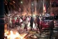 Firecrackers explode near protesters during clashes with police in Jakarta in May. Photo: AP