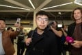 Hong Kong activist Joshua Wong (centre) arrives at Tegel Airport in Berlin on Monday. Photo: EPA-EFE