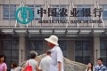 People walk past the headquarters of the Agricultural Bank of China in Beijing. New loans growth in China declined in August. Photo: AFP