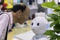 An attendee looks at a CloudMinds Technology's Cloud Pepper semi-humanoid robot at the World Artificial Intelligence Conference in Shanghai in August. Photo: Bloomberg