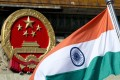 The Indian national flag is flown next to the Chinese national emblem in Beijing. Photo: AP