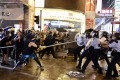 Protesters attack police officers in Tsuen Wan on August 25. An officer then fired a warning shot, the first time since the protests began in June. Photo: Xinhua