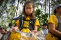 12-year-old Ralyn Satidtanasarn, known by her nickname Lilly, collects plastic waste during a clean-up by Thai NGO Trash Hero at the Khung Bang Kachao urban forest and beach in Bangkok. She paddles the city's canals picking up plastic and other waste, sometimes skipping class to do so. Photo: Mladen Antonov/AFP