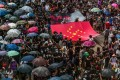 Protesters march through Central on August 31 with a banner on which the stars of the Chinese flag have been rearranged into a Nazi swastika. Photo: AFP