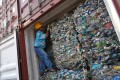 An officer stands inside a container full of plastic waste at Tanjung Priok port in Jakarta. Photo: Antara Foto via Reuters