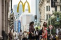 Pedestrians and shoppers walk past a McDonald's restaurant in Shanghai. The fast-food chain's revenues in China have grown as consumers increasingly order food using online delivery apps. Photo: Bloomberg