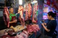 A customer pays a butcher using her smartphone at a market in Beijing. Photo: AFP