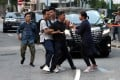 A protester is escorted by undercover police officers after he tries to stop Chief Executive Carrie Lam's motorcade on September 26. Photo: Reuters
