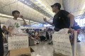 Protesters distribute food and water to passengers at Hong Kong airport on August 14 and apologise for the disruption they caused the day before. Photo: Kimmy Chung