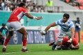 Argentina back row Javier Ortega Desio passes the ball as he is tackled during his team's match against Tonga at the 2019 Rugby World Cup. Photo: AFP
