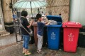 A child puts plastic delivery bags into a recycling bin. Photo: EPA