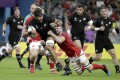 New Zealand's Patrick Tuipulotu is tackled by a Canadian defender during their game in Oita, Japan. Photo: AP