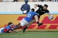 New Zealand's T J Perenara looks to score a try as he is tackled by Namibia's Helarius Kisting during the Rugby World Cup pool B game at Tokyo Stadium. Photo: AP