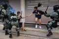 Hong Kong police chase down a woman wearing a face mask in the city's central district on Saturday. Photo: AFP