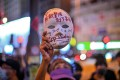 A woman holds a mask with slogans written on it as protesters gather outside Mong Kok police station in Hong Kong on October 5, a day after the anti-mask law came into effect. Photo: AFP