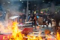 Protesters throw cardboard into a fire in Central, Hong Kong, on October 1. As China celebrated the 70th anniversary of the founding of the nation, clashes between police and protesters took place in 13 different locations across the city. Photo: Bloomberg