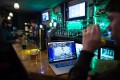 A gamer drinks a beer as he takes part in a Hearthstone tournament in London. Photo: AFP