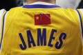 Following the anti-NBA fallout, a fan is seen wearing a LeBron James jersey with the NBA logo covered by a Chinese national flag, during a match between the Los Angeles Lakers and Brooklyn Nets at Shanghai's Mercedes-Benz Arena, on Thursday, October 10. Photo: Reuters