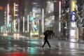 A man walks a pedestrian crossing at Ginza shopping district in the pouring rain because of Typhoon Hagibis in Tokyo on Saturday. Photo: AP