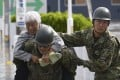 A local resident is rescued by Japanese Self-Defence Forces soldiers in Motomiya, Fukushima prefecture. Photo: Kyodo