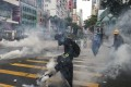 Anti-government protesters react to tear gas in Wan Chai following a rally in defiance of the anti-mask law issued by the government on October 5, 2019. The months-long protests have hit Hong Kong's economy hard. Photo: Sam Tsang