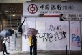Demonstrators spray paint a security camera at a Mong Kok branch of the Bank of China. Photo: Bloomberg