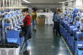 Staff members arrange cotton socks on a fully automatic hosiery machine at a knitting company in northwest China in 2017. Photo: Xinhua
