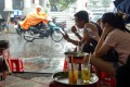 People use smartphones as they sit and drink tea by the roadside in Hanoi, Vietnam, which plans to become a cashless economy by 2027. Photo: Bloomberg