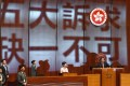 """The words: """"Five demands, not one less"""", are projected by pro-democracy lawmakers onto the wall behind Chief Executive Carrie Lam as she prepares to deliver her policy address in the Legislative Council in Hong Kong, on October 16. Photo: EPA-EFE"""