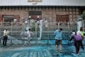 Volunteers help clean up Kowloon Mosque in Tsim Sha Tsui on Sunday after a police water cannon sprayed the building with blue-dyed water. Photo: Handout