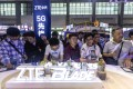 People visit a ZTE booth during the Big Data Expo in Guiyang, Guizhou province, on May 26. Guizhou is the site of China's first big data pilot zone, attracting companies such as Apple, Qualcomm, Huawei, Tencent, Alibaba and Foxconn. Photo: EPA-EFE