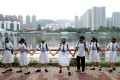 Masked students in school uniform form a human chain along Shing Mun River in Sha Tin as part of an anti-government protest on September 19. Photo: Reuters