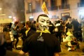 A demonstrator wears a Guy Fawkes mask during a general strike in Catalonia, Spain. Photo: Reuters