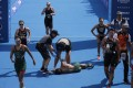 Mexico's Cecilia Perez (centre) collapses after competing in a women's triathlon test event at Odaiba Marine Park, a venue for marathon, swimming and triathlon at the Tokyo 2020 Olympics. Photo: AP