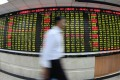 An investor passes by an electronic board displaying stock prices at a brokerage house in Shanghai on August 8, 2011. Photo: Xinhua