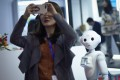 A robot watches a woman using her mobile phone at China Beijing International High-Tech Expo in Beijing on October 24. Photo: AFP