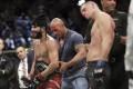 Dwayne 'The Rock' Johnson places the 'BMF' belt on Jorge Masvidal as Nate Diaz looks dejected. Photo: AP