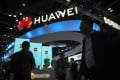 Attendees walk past a display for 5G services from Chinese technology firm Huawei at the PT Expo in Beijing, Oct. 31, 2019. Photo: AP