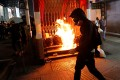 A protester walks past a burning barrier outside Mong Kok MTR station on October 27. Photo: Reuters