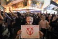 Anti-government protesters with Guy Fawkes masks in Tsim Sha Tsui on Tuesday. Photo: Felix Wong