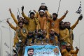 Supporters of the Islamist Jamiat Ulema-e-Islam party wave flags from atop a vehicle during the anti-government Azadi (Freedom) March. Photo: AFP